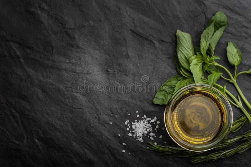 Olivenöl mit verschiedenen Grüns auf der rechten Seite der schwarzen Steintabelle stockfotografie