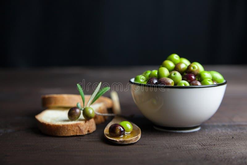 Olivenöl und Brot auf Holz lizenzfreies stockbild