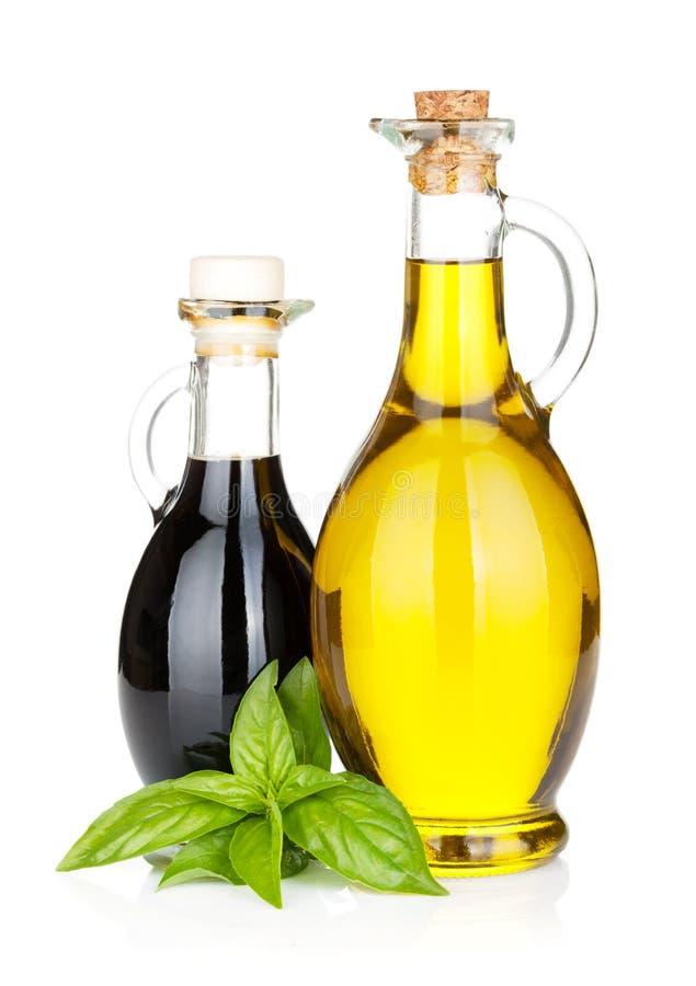 Olivenöl- und Essigflaschen mit Basilikum stockfotos