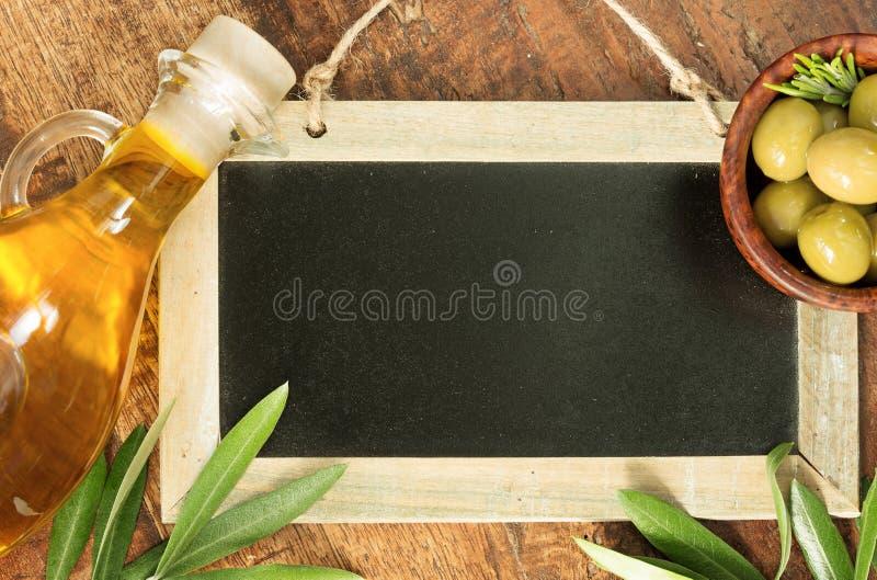 Olivenöl und grüne Oliven auf Tafel lizenzfreies stockbild