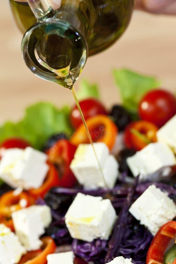 Olivenöl, welches das Schütten auf frischen Salat kleidet stockfotografie