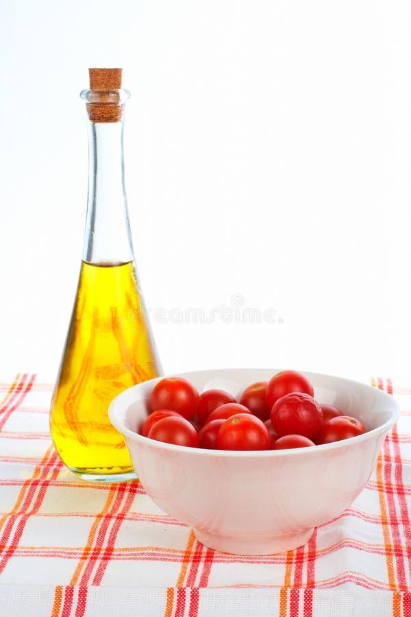Olivenölflasche und rote Tomatekirsche stockbild