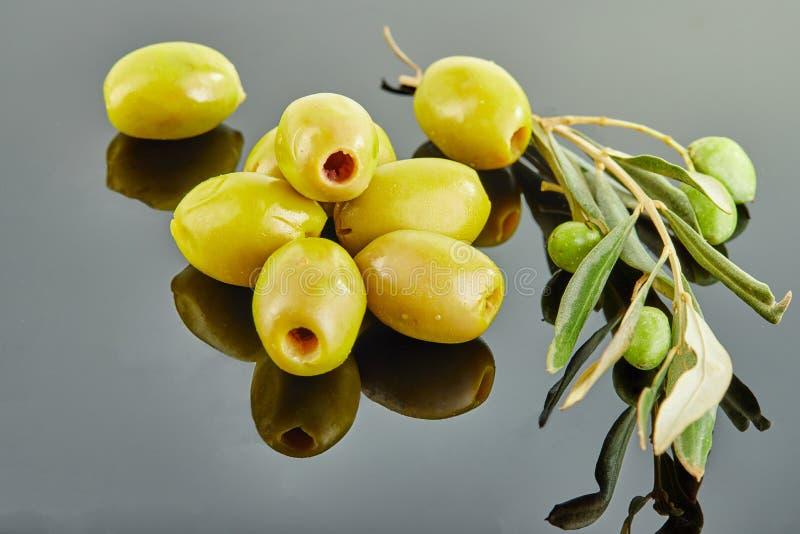Oliven mit einer Niederlassung eines Olivenbaums mit den Früchten, die in einem Dia auf einem grauen Hintergrund liegen lizenzfreies stockfoto