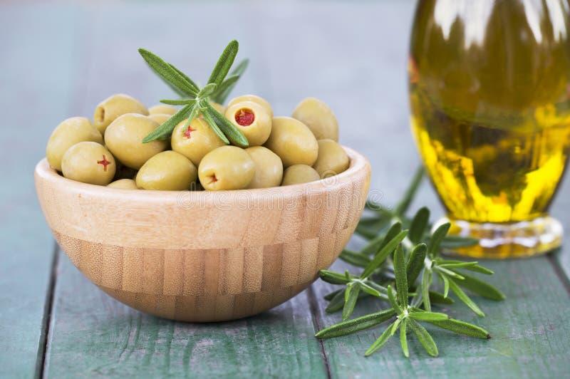 Oliven mit reinem Öl und Rosmarin stockfotografie