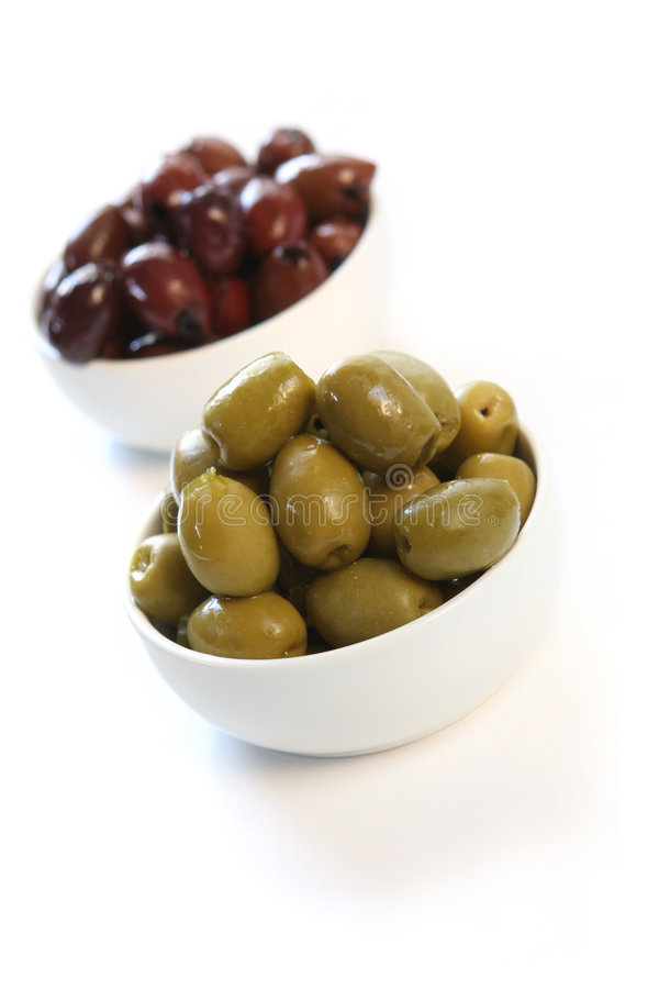 Olives. Green and black olives in small white bowls. Shallow depth of field, high-key effect royalty free stock image