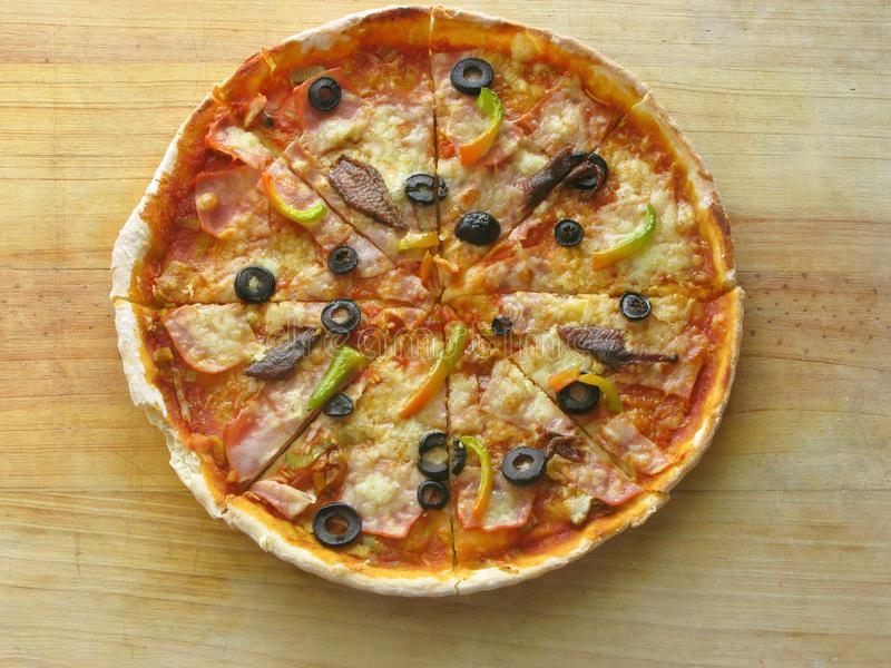 Olives and anchovie`s pizza. Olives, pepper, ham, cheese and tomato sauce Italian pizza in a wooden table royalty free stock images