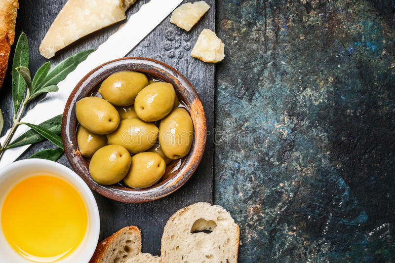 Olives appetizer with cheese, oil and ciabatta gut slices on dark rustic background, top view. Place for text. Italian food stock images