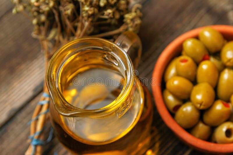 Olives avec le paprika dans une cuvette en céramique de rétro style, la brindille du basilic sec et le broc avec l'huile d'olive photographie stock libre de droits
