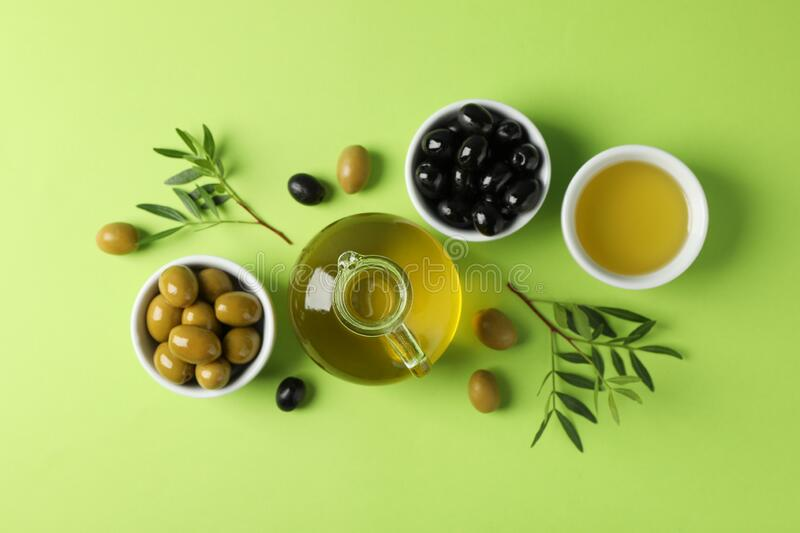 Olives, bottle and bowl with olive oil on background, top view. Olives, bottle and bowl with olive oil on green background, top view stock photography