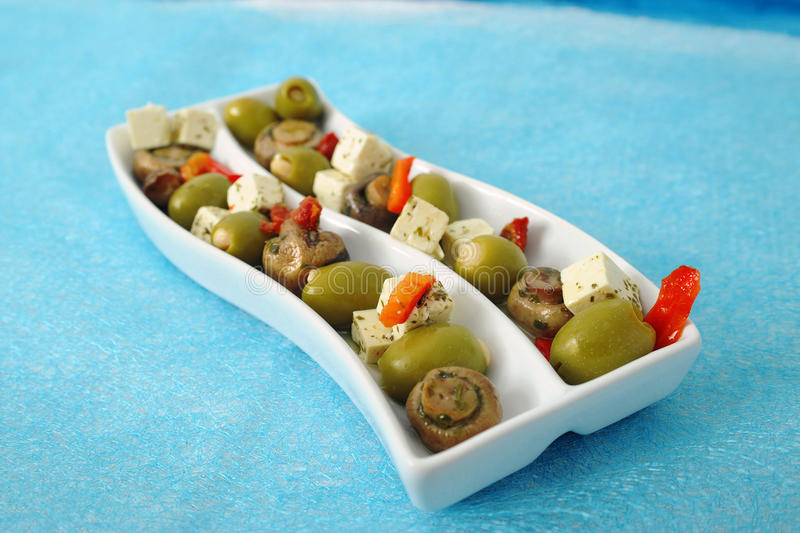 Olives, Cheese and Mushrooms. Relish tray filled with green olives, mushrooms, pieces of cheese and pimento stock image