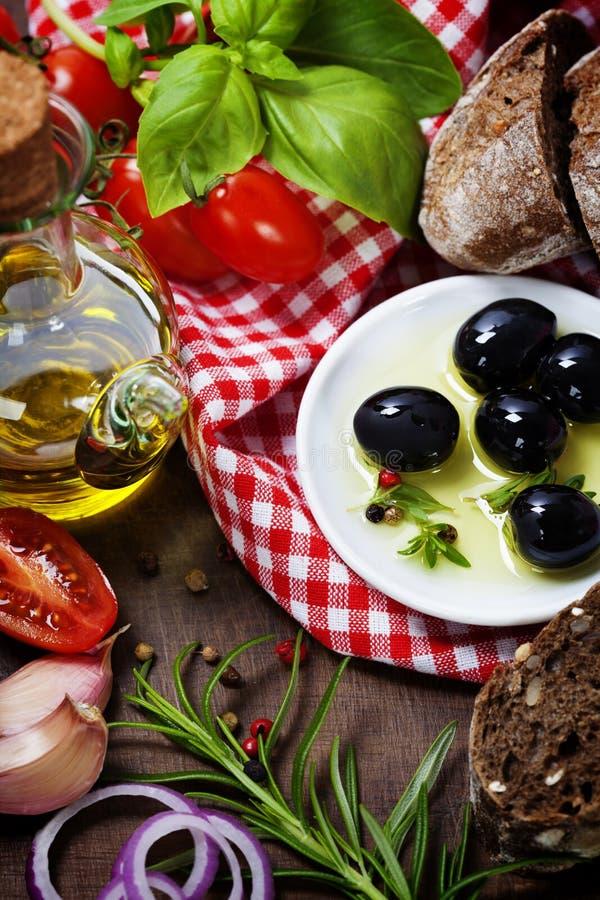 Olives et Olive Oil sur un vieux tablel photographie stock