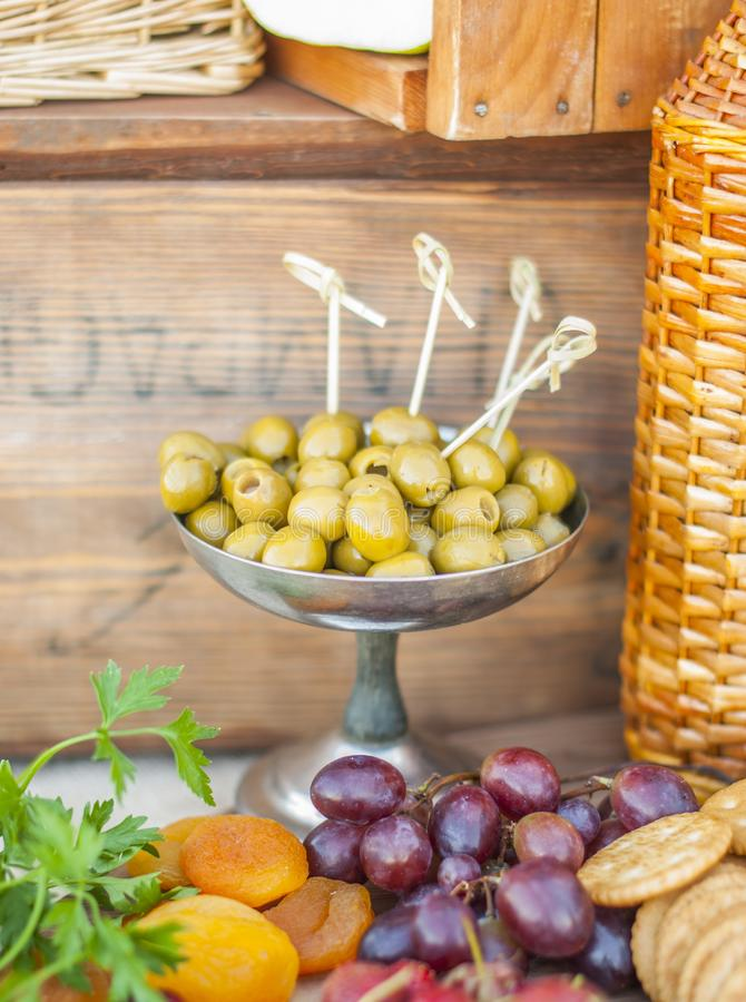 Olives and fruits on a beautifully vintage decorated table. Olives and ts on a beautifully vintage decorated table. Outdoor reception royalty free stock photo