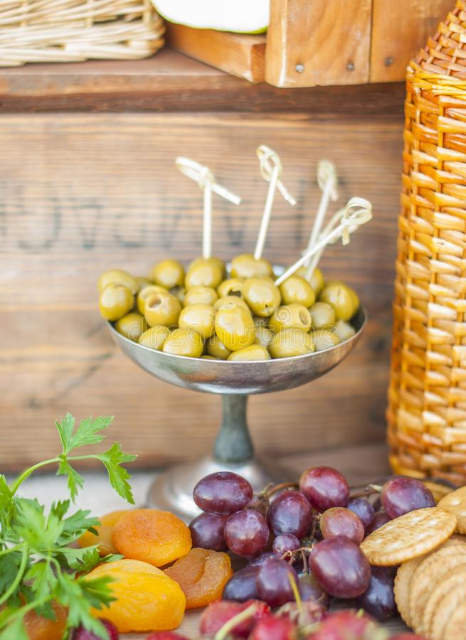 Olives and fruits on a beautifully vintage decorated table. Outdoor reception royalty free stock images