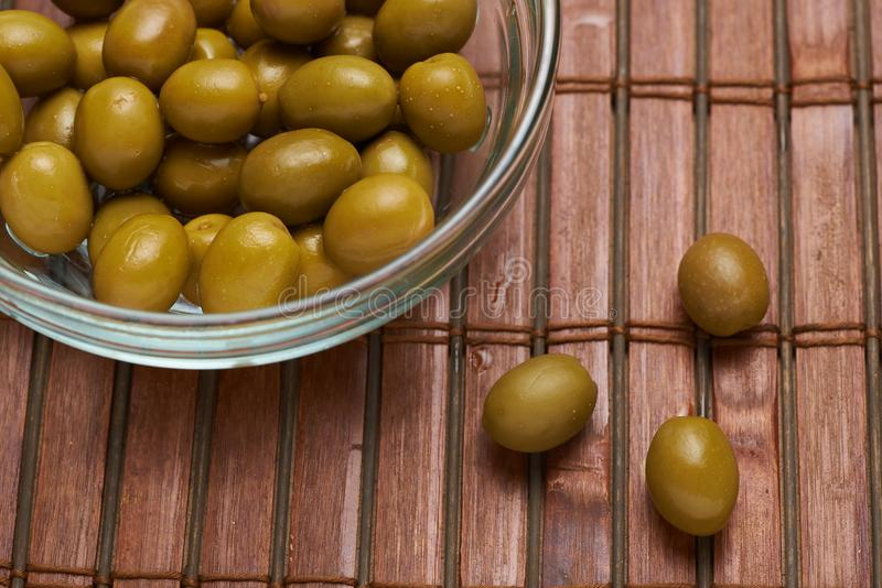 Olives in a glass plate on a brown background royalty free stock images