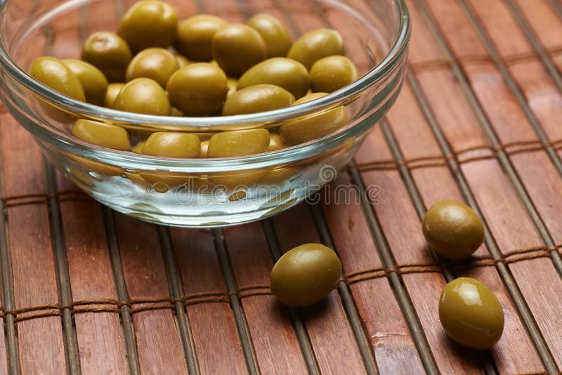 Olives in a glass plate on a brown background royalty free stock image