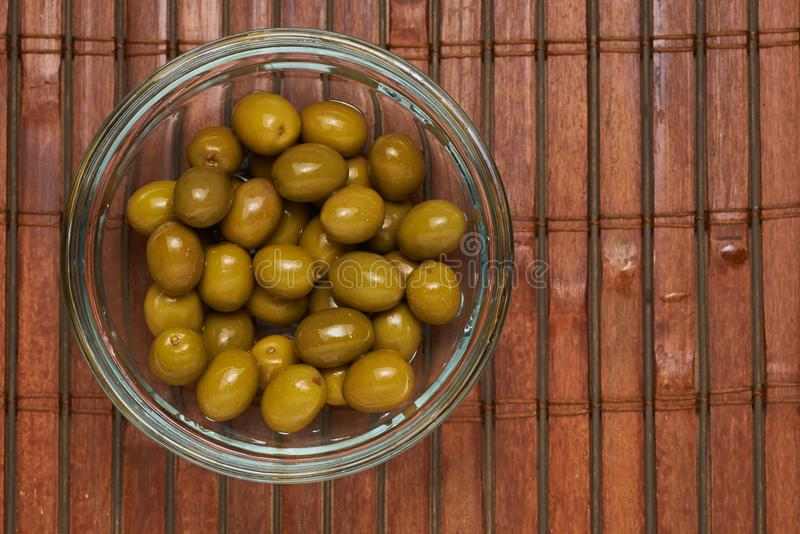 Olives in a glass plate on a brown background stock photography