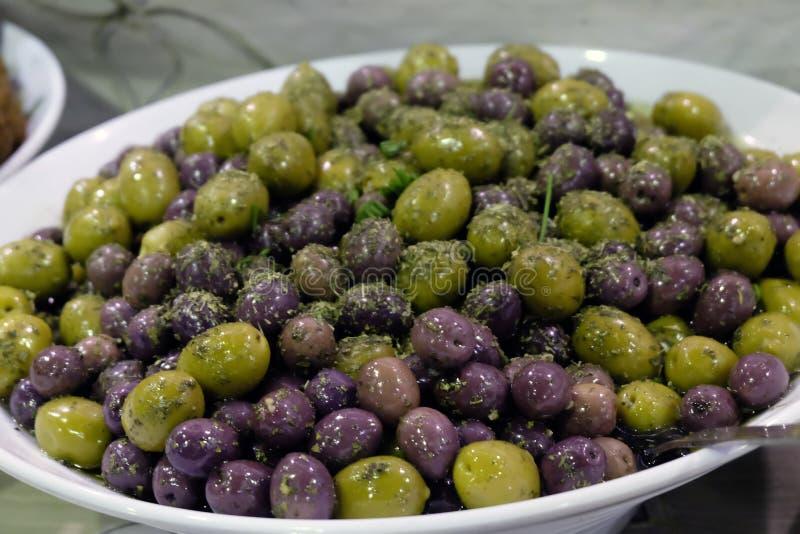 Olives mélangées arrosées avec des herbes dans une cuvette blanche photographie stock libre de droits