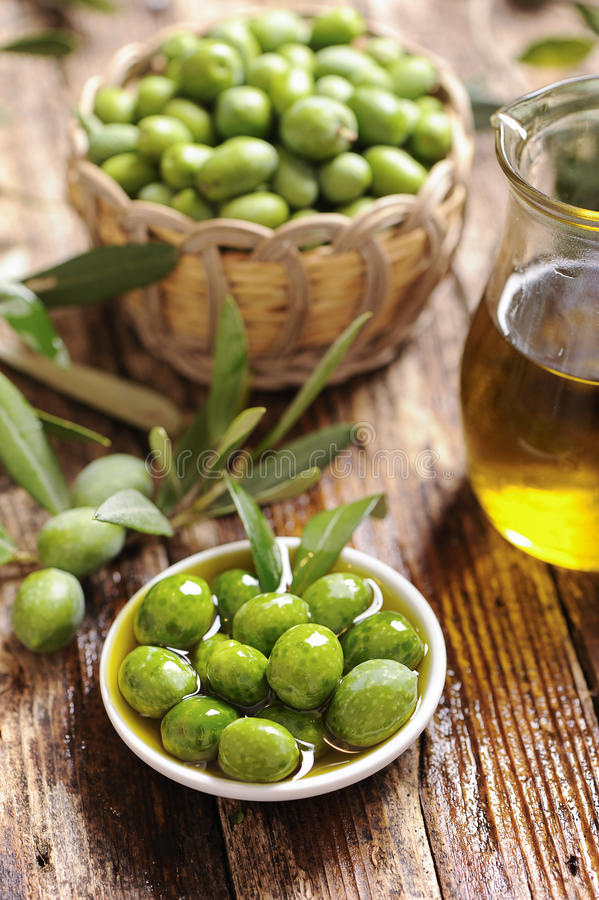 Olives and Olive Oil. On wooden table stock photos