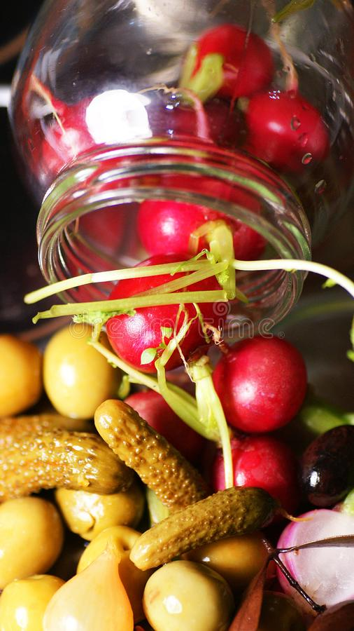 Olives, pickles and radishes coming out of a glass jar royalty free stock images