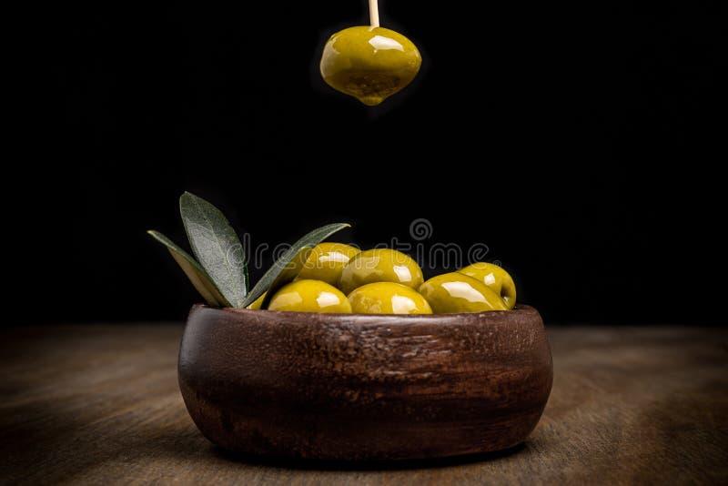 Olives vertes et feuilles sur une table en bois avec le fond noir image libre de droits