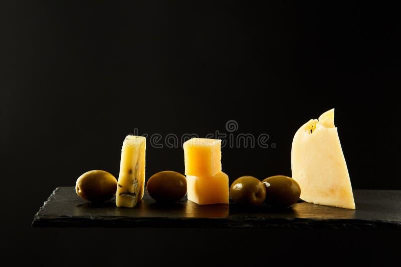 Olives vertes et morceaux savoureux de fromage à pâte dure frais placé sur le fond noir photos stock