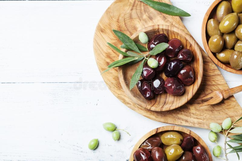 Olives in wooden bowls decorated with fresh olive tree branch on white kitchen table top view. royalty free stock image