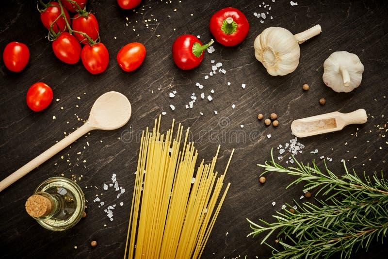 Olivgrüne Pfeffer und Teigwaren des Tomatenknoblauchsalzes auf einer schwarzen Tabelle stockbilder