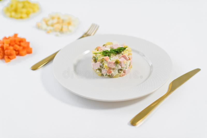 Olivier salad and ingredients for cooking on a white background. royalty free stock photo