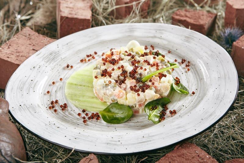 Olivier Salad of Russische Salat met Zalm en Rode Kaviaar op Ret stock foto