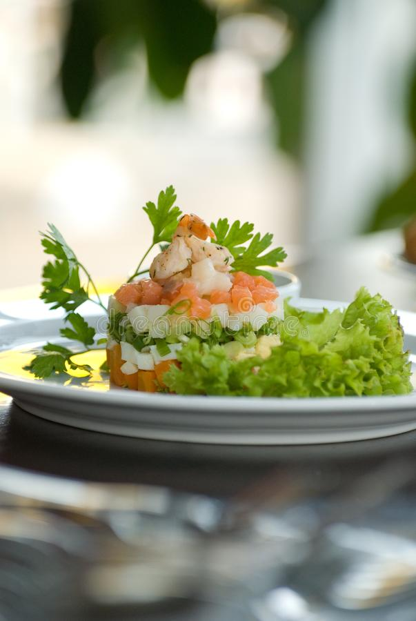 Olivier salad with shrimps, eggs and vegetables on a white plate stock photo