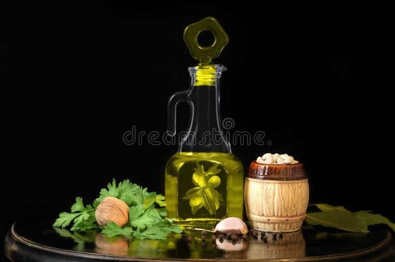 Olivolja, bönor och kryddor på en svart bakgrund royaltyfri fotografi
