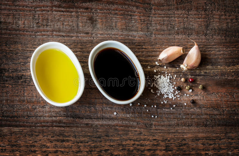 Olivolja balsamic vinäger, vitlök, saltar och pepprar - ättiksåsdressingen fotografering för bildbyråer
