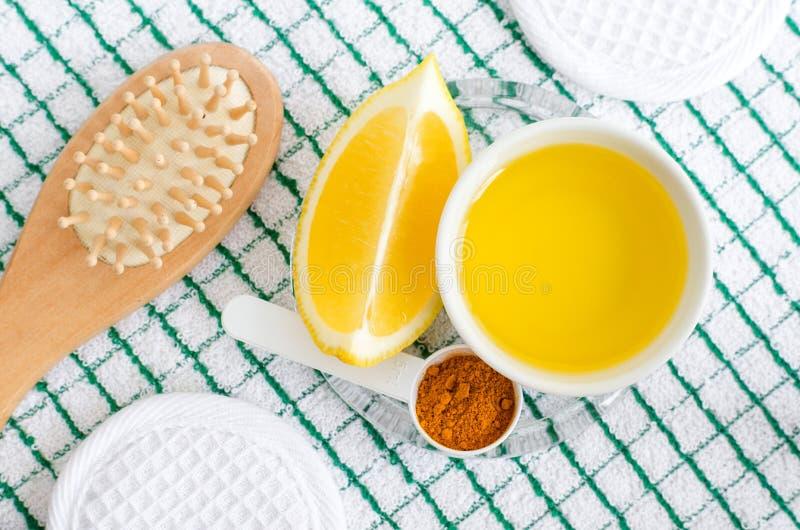 Olivolja, citron, gurkmejapulver och tr?h?rborste Ingredienser f?r att f?rbereda den diy framsidan och h?rmaskeringar och fuktigh fotografering för bildbyråer