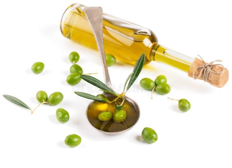 Olivolja i en glasflaska och gröna oliv arkivfoton