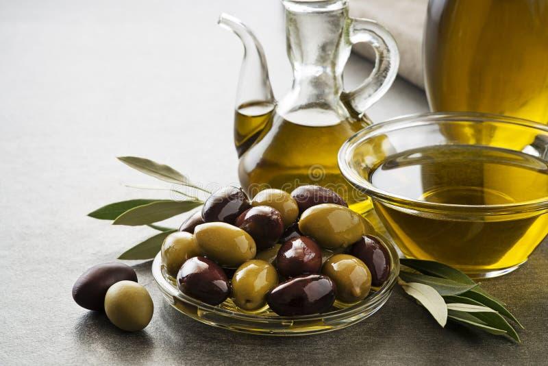 Olivolja i flaska med oliv fotografering för bildbyråer