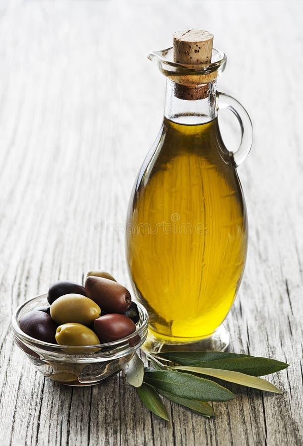 Olivolja i flaska med oliv arkivbilder