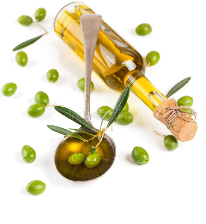 Olivolja i glasflaska med oliv arkivbild