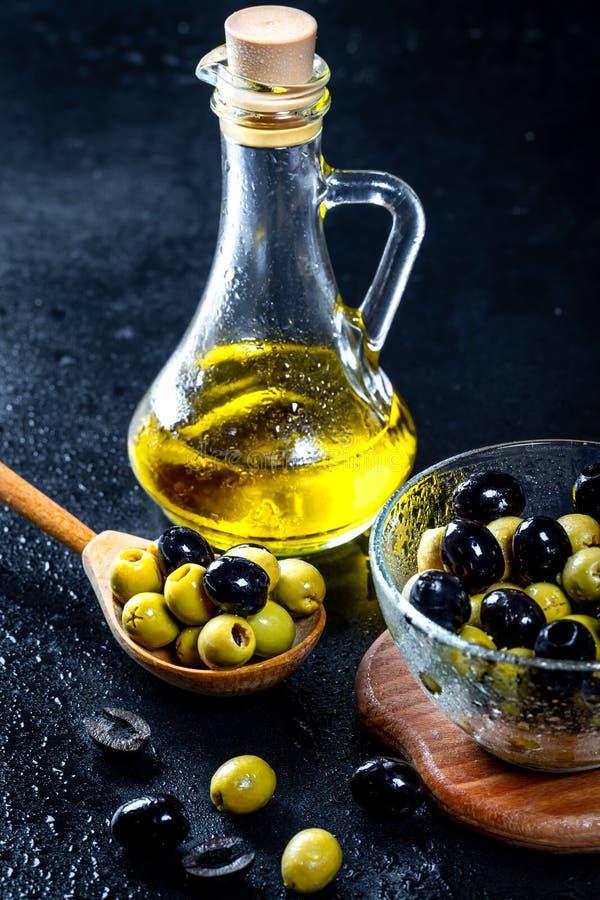 Olivolja i tappningglasflaskor med svarta gröna oliv och träskeden på svart bakgrund Copyspace flatley Mat fotografering för bildbyråer