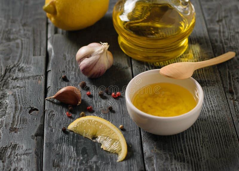 Olivolja med vitlök och citronen i en vit bunke på en mörk svart tabell Dressingen för bantar sallad royaltyfri fotografi
