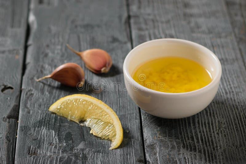 Olivolja med vitlök och citronen i en vit bunke på en mörk tabell Dressingen för bantar sallad arkivbilder