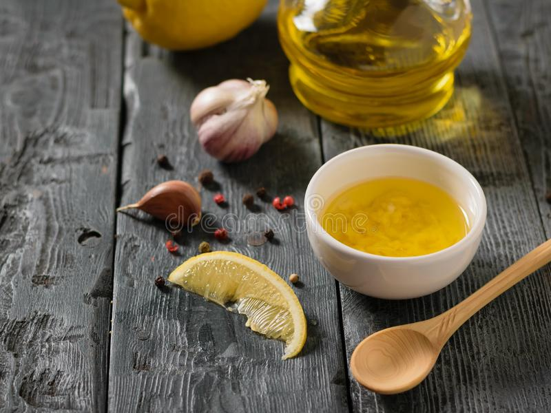 Olivolja med vitlök och citronen i en vit bunke på en trätabell Dressingen för bantar sallad fotografering för bildbyråer