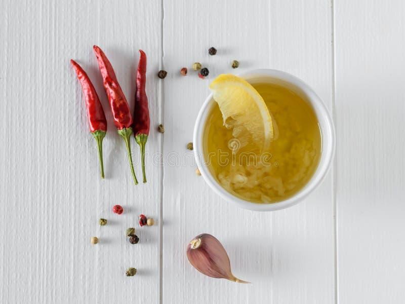 Olivolja med vitlök, peppar och citronen i en vit bunke på en vit tabell Dressingen för bantar sallad övre sikt royaltyfria foton