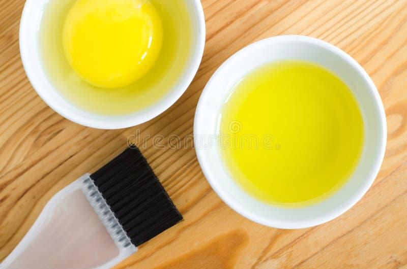 Olivolja och det rå ägget i små keramiska bunkar för att förbereda den hemlagade brunnsorten vänder mot och hårmaskeringar Ingred arkivbild