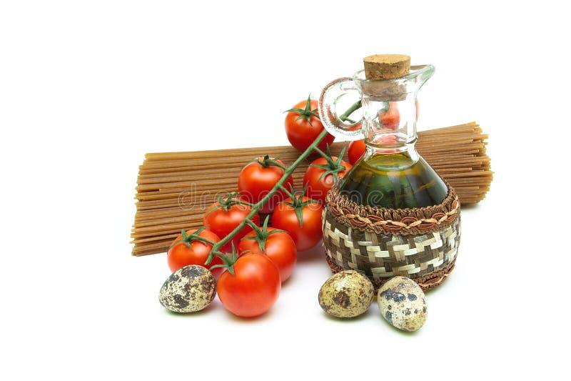 Olivolja, pasta, tomater och ägg på en vit bakgrund fotografering för bildbyråer