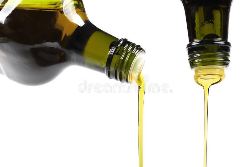 Olivolja som häller från glasflaskan arkivfoton