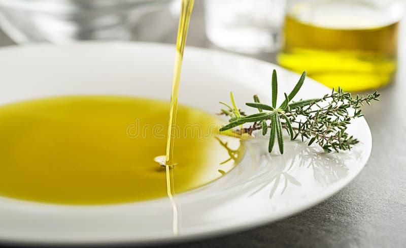 Olivolja som häller med kryddor och örter för att plätera tätt upp arkivbilder