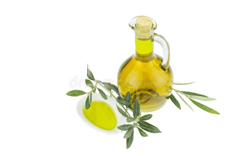 Olivoljaflaska och bunkeplatta med den olivgröna filialen Jungfrulig olivolja Naturlig olivolja, sund mat royaltyfria bilder