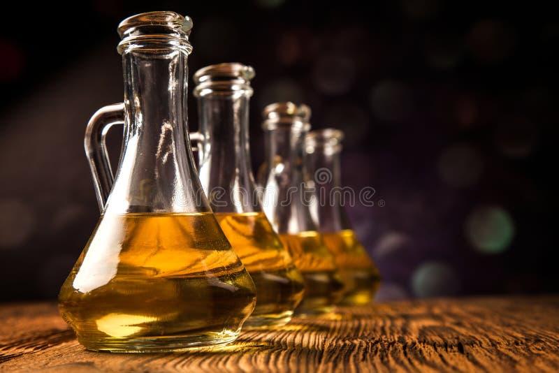 Olivoljor i flaskor med ingriedients arkivbilder