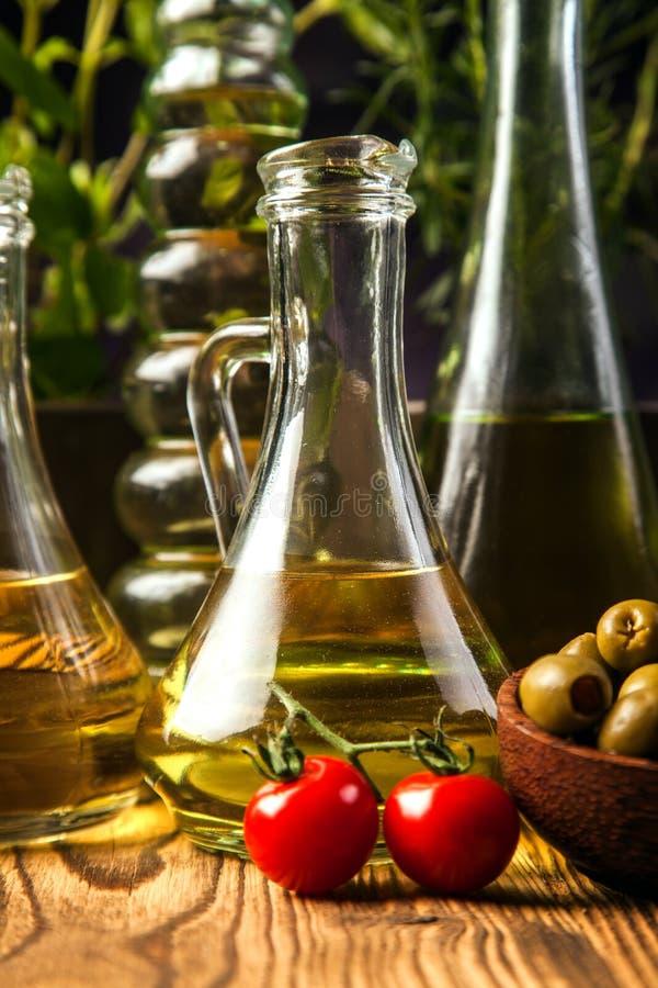 Olivoljor i flaskor med ingriedients arkivfoton