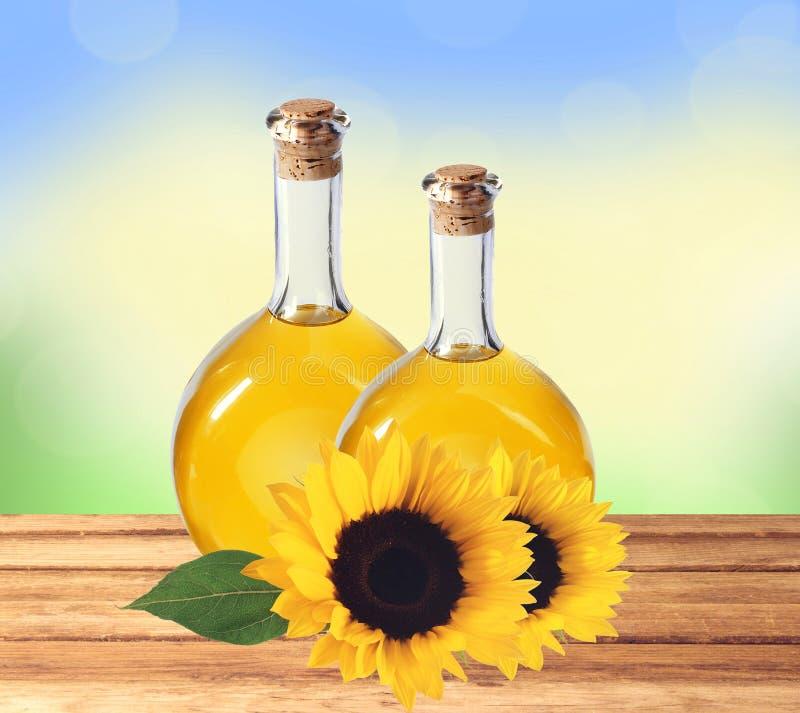 Oliwi w butelkach i słonecznikach na drewnianym stole nad naturą fotografia royalty free